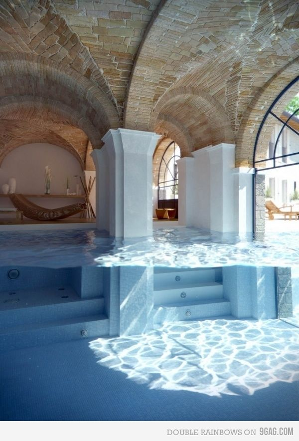 very nice swimming pool that leads to the inside of the house and also has a portion outside of the house.
