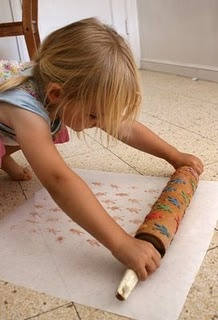 """Make a fun print with foam stickers on a rolling pin. Would be great for do-it-yourself wrapping paper or silly kid's """"wall paper"""""""