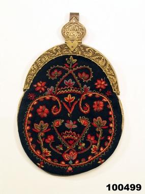 Kjolsäck, 'lûmsäck. Av svart ylle med flerfärgat ullgarnsbroderi, bakstycke av skinn. Låsbyglar av mässing, ornerade, hake av järn och mässing. Från Orrmo
