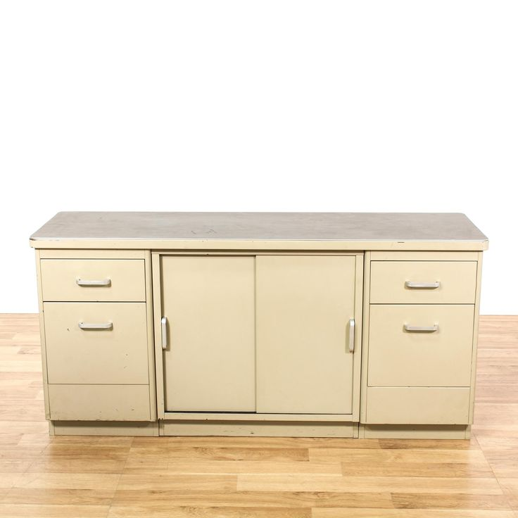 This industrial storage cabinet is featured in a durable metal with an off white beige paint finish. This mid century office credenza has 4 file drawers, sliding panel doors with interior storage and shiny nickel hardware. Perfect for storing files and paperwork in an office! #americantraditional #storage #cabinet #sandiegovintage #vintagefurniture