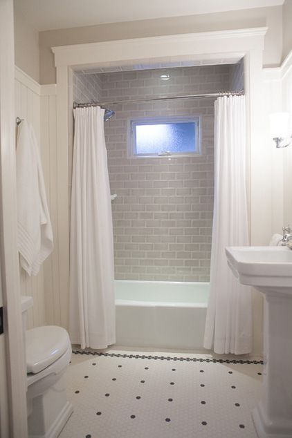 grey subway tile bathroom; black  white tile floor, crown molding, window in shower
