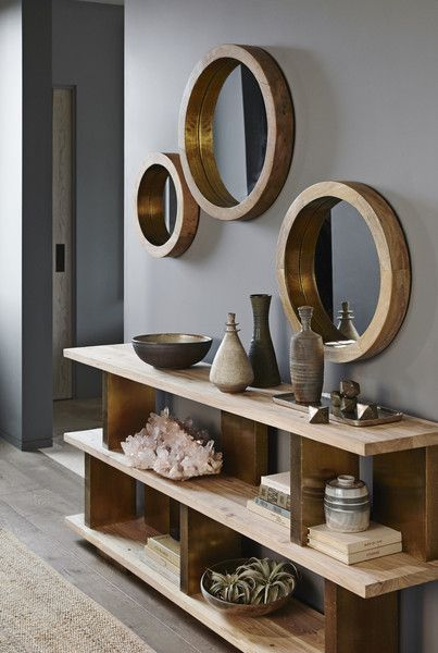 Round mirrors are held by thick wooden frames that evoke the glamour of a luxury liner. Shiny brass trim on the inner rim accentuates the clean and simple desig
