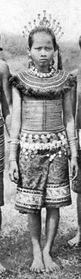 Sea Dayak (Iban) woman from Rejang, Sarawak, wearing rattan corset decorated with brass rings and filigree adornments. c. 1910