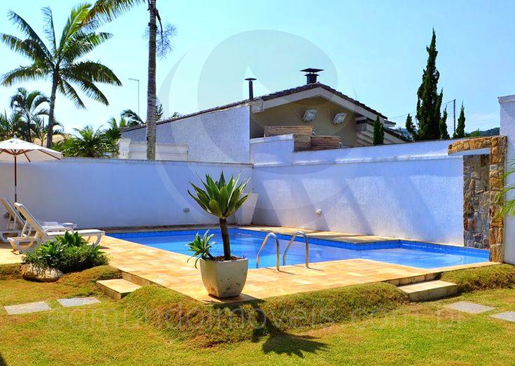 Um caminho gramado conduz à piscina, margeada por pedra mineira e revestida com azulejos azul turquesa.