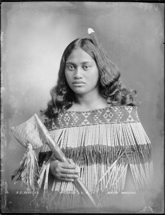 Maori woman photographed by Frank J Denton, circa 6 April 1904, probably in the Wanganui region. She is wrapped in a taniko bordered cape, and has a white tipped feather in her hair. She holds a tewhatewha (Maori fighting staff).