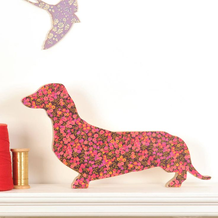 A freestanding, wooden dachshund sausage dog, the front covered with liberty print fabric. You can choose to have a message engraved on the reverse. And would you like this little dog engraved? We can add your choice of words to the reverse. We have many colours of Liberty fabric so do let us know if you have a specific idea. We have broken the colours down to the follwoing: violet, pale pink, bright pink, green, light blues, dark bluesOur freestanding, wooden dachshund sausage dog is faced…