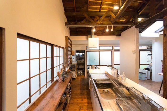 すっきりと片付けられたキッチン。シンクは、友人が暮らしていた取り壊されるアパートからもらってきたもの。クリーム色の扉を白く塗り、取っ手も付け替え、回りにカウンターを組んで大きなアイランドキッチンに。