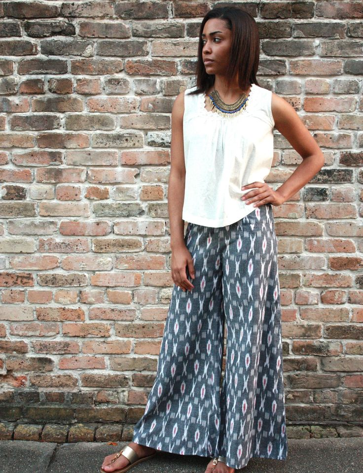 Wide leg, palazzo pants in an ikat grey diamond print. These super comfy, chic pants feature a flat front waistband in the front and an elastic waistband in the back.  Available with or without the side slit on the outer leg. The slit reaches just below the knee and allows the pants to be tied up for a more funky look. If left untied the pants will elegantly flow in the wind like a maxi skirt. Fair trade. Handwoven ikat fabric.