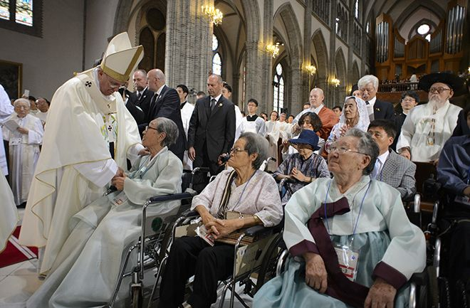 "Taking action: Pope Francis greets ""comfort women"" as he arrives to celebrate a Mass for peace and for the reconciliation of North and South Korea at Myongdong cathedral in Seoul, South Korea, on August 18. The Pope, together with leaders of the world's major religions, pledged to help eradicate human slavery and trafficking by 2020. Photo: CNS/L'Osservatore Romano"