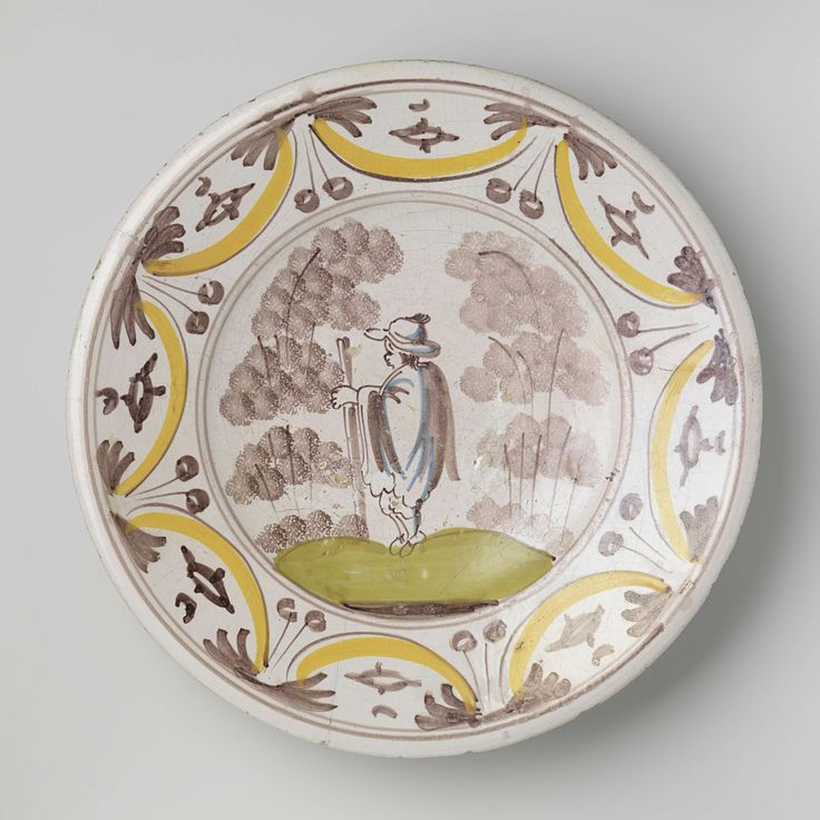 Anonymous | Schotel, Anonymous, c. 1680 - c. 1750 | Ronde schotel van veelkleurig beschilderde majolica. Op het plat is een landschap met bomen geschilderd waarin een naar links lopende man met een hoed op en een stok in zijn linkerhand. De man draagt een lange jas of een cape. Op de rand zijn acht segmentbogen geschilderd waarbinnen een grof aangebrachte versiering.