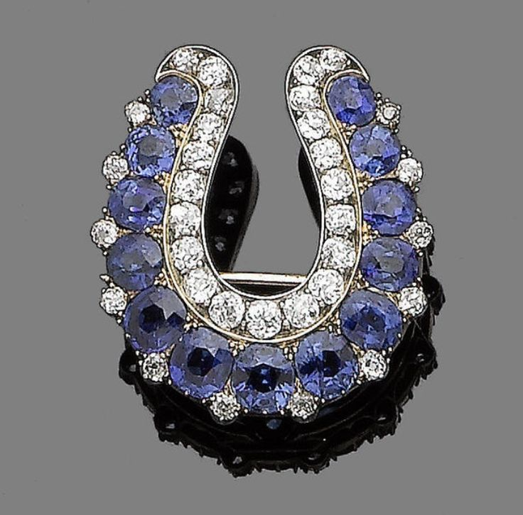 A sapphire and diamond brooch/pendant, circa 1890.  Designed as a horseshoe, set with a row of cushion-shaped sapphires, to an inner row of old brilliant-cut diamonds, with similarly-cut diamond pointers, mounted in silver and gold, diamonds approx. 1.90cts total, length 3.0cm