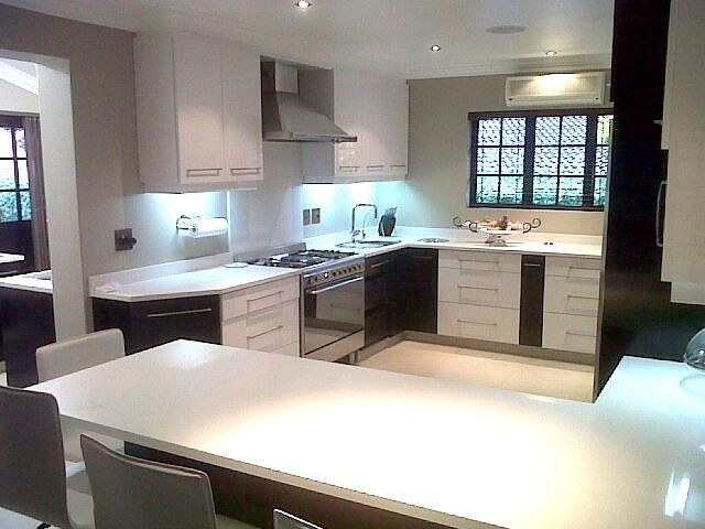 Two tone Kitchen with Niemann High gloss white doors and Sapele veneer stained dark Mahogany doors. White Ceasar stone counters. Done by Dolphin Coast Kitchens tezcraig@gmail.com
