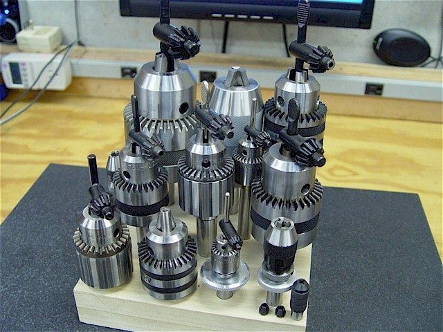 Thirteen drill chucks of various sizes and arbors in a wooden stand for 9x20 lathe.