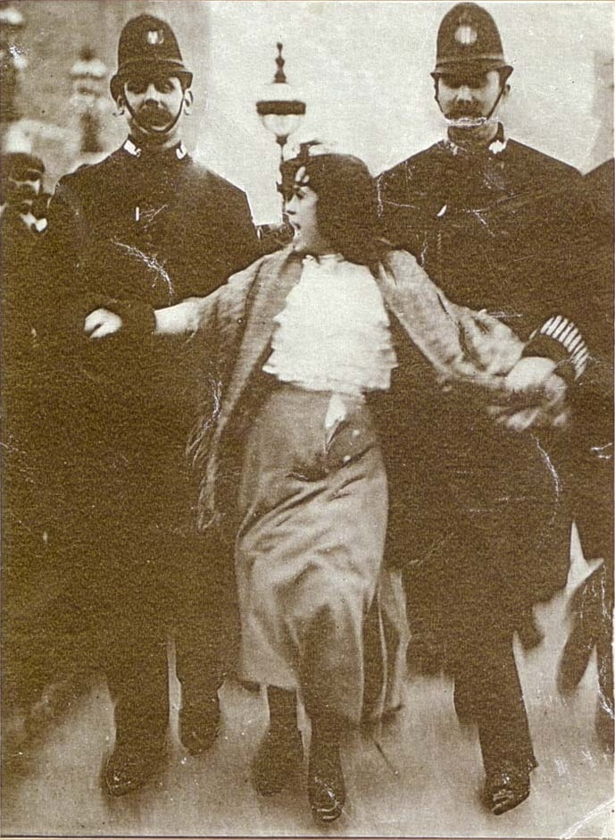 "BAD REPUTATION identifies the woman in the iconic photo: ""on the front page of the Daily Mirror: a young woman, flanked by a pair of police officers. Her skirts and shawl are in disarray, her hair wild. She appears to be shouting. Her name is Dora Thewlis, a weaver in a Huddersfield mill. She is just sixteen years old."" Read her story."