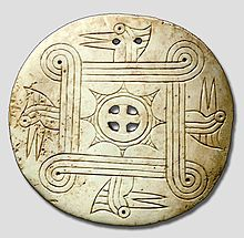 """1250-1450 CE.[1] The Cox Mound gorget style features four woodpecker heads facing counter-clockwise, a four-lopped square motif, and a cross within a rayed circle. The four-looped square, or guilloche, is considered by some to be a """"whirling sun"""" motif, or a priestly or chiefly litter;[17]Woodpeckers are considered warrior birds, medicine birds, or sometimes the four winds by Cherokee. (Click picture to learn more.)"""