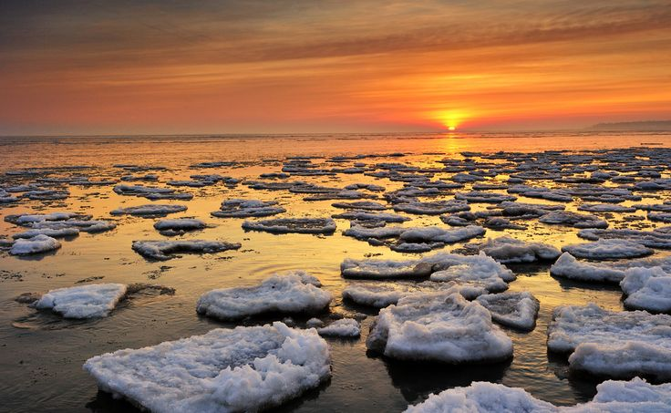 Ice floats on Lake Huron during a winter sunrise near Port Hope, Michigan.