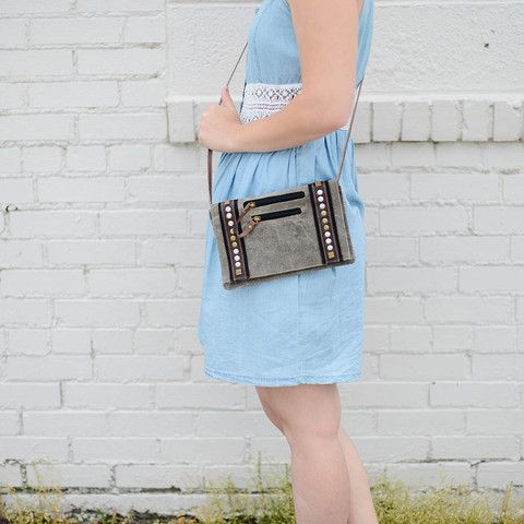 Melrose Small Cross-body Bag. Take a stroll with our Melrose crossbody. It will be a conversation piece everywhere you go. It features beautiful metal accents on a grayish khaki canvas and two front pockets, perfect for your lipstick and keys. Seriously the perfect little crossbody! One left at Nora Gray! An Indiana boutique located in Berne, IN and online at www.nora-gray.com