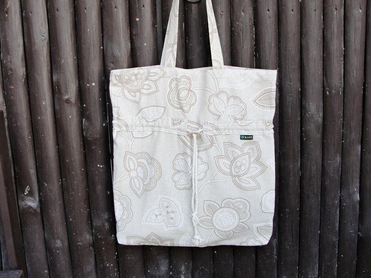 Moderní stylová taška přes rameno nebo do ruky vhodná na výlety pro nákupy nebo k vodě. Velmi pevné bavlněné plátno v béžovém tónu s dekorem květin. Ve dvou třetinách tunýlek na stažení kabelky. Ideální pro každodenní nošení.