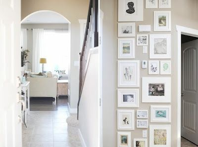 All white frames displayed on narrow hallway wall