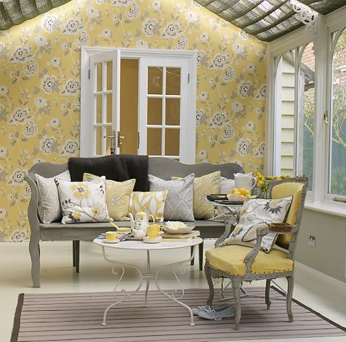 Pretty use of yellow, white and grey in this bright Garden Room. Non upholstered painted bench is softened by a mountain of cushions in toning colours and the floral wallpaper acts the adhesive to tie the whole look together. Tea anyone?