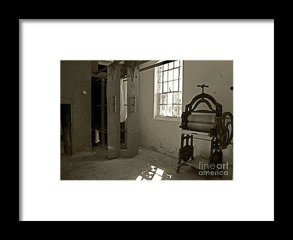 Drying racks in the wash-house are beside the rustic clothes wringer in Southwell workhouse in England.