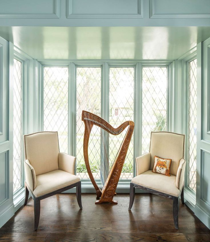 Beautiful architectural detail and molding painted soft aqua green in a traditional room with harp and arm chairs. Design by The Fox Group. #traditionalstyle #interiordesign #harp #livingroom