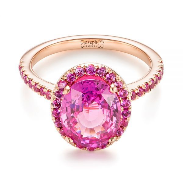 #103630 This gorgeous engagement ring features an oval pink sapphire prong set at the top, accented by a halo of split prong set pink sapphires, and additional pink sapphires...