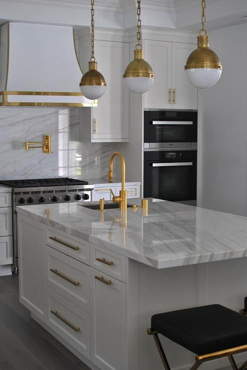 love most of this white and gold kitchen white kitchen with gold accents kitchen range hood brass hicks pendants pot filler faucet marble