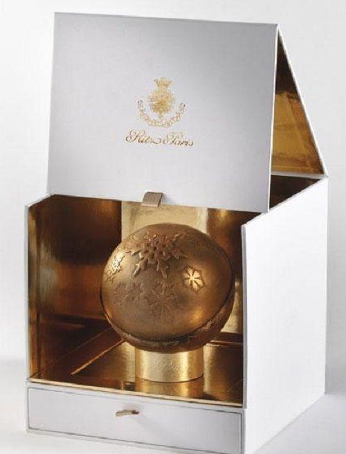 Bûche Boule de Noël du Ritz  Le Ritz reste sur le thème du chocolat pour sa « bûche » de Noël qui prend la forme cette année d'une boule dorée. Sous la poudre scintillante se dévoile du chocolat craquant qui renferme une mousse pralinée. Le coeur du dessert contient un biscuit dacquoise à la noisette enrobé d'une marmelade et d'un crémeux d'orange.