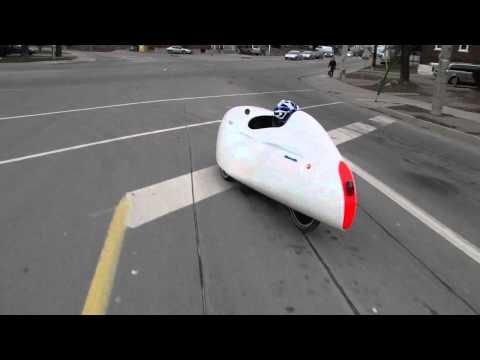 A velomobile is a human powered vehicle, generally a trike, with an aerodynamic shell for comfort, weather protection and luggage space.