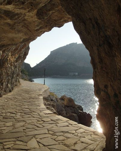 The outline of #Palamidi Castle on the top of the hill seen through the hole in the rock along #Arvanitia promenade in #Nafplio. #Peloponnese - #Greece