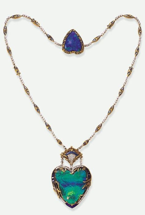 A SUPERB BELLE ÉPOQUE OPAL PENDANT NECKLACE. Centring upon a heart-shaped opal pendant, within a calibré-cut sapphire, old European-cut diamond and blue enamelled frame, enhanced by sculpted scrolling gold iris motifs, suspended by twin diamond collet lines from a fan-shaped surmount, to the chain of alternating diamond collets and navette-shaped enamelled foliate motif links, joined to a heart-shaped opal within a gold iris motif frame, mounted in gold and platinum, circa 1900, numbered.