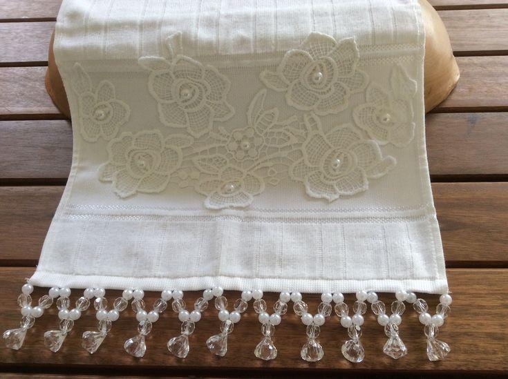 Toalha de lavabo com renda e pedrarias, na cor branca. Medida 30x45cm.