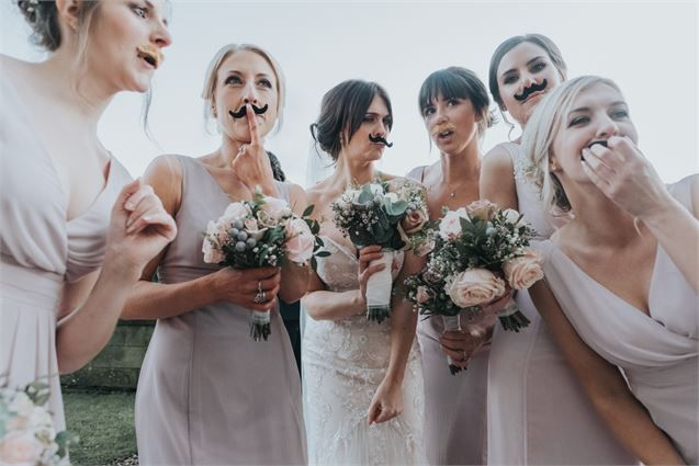 Cheeky bridesmaid photo with the bride on the wedding day. Playful props like these moustaches are a great addition to wedding photography. Gorgeous blush pink bouquets with rose and foliage look great with dusky pink bridesmaid dresses. Photo by Ivory Fayre Photograpy and Videography