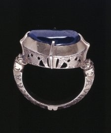 Finger-ring; gold; oval bezel, its sides decorated in openwork with engraved birds; set with a carbouchon sapphire held in four claws; the junction between bezel and hoop decorated with two animal heads; the hoop trapeziodal in section with beaded outer edge, the two sides engraved to receive a nielloed inscription: AVE MARIA GRA / TIA PLENA DMI. ('Hail Mary, full of the grace of the Lord'), a variation on the angelic salutation at the Annunciation    Made in England or France    13th C