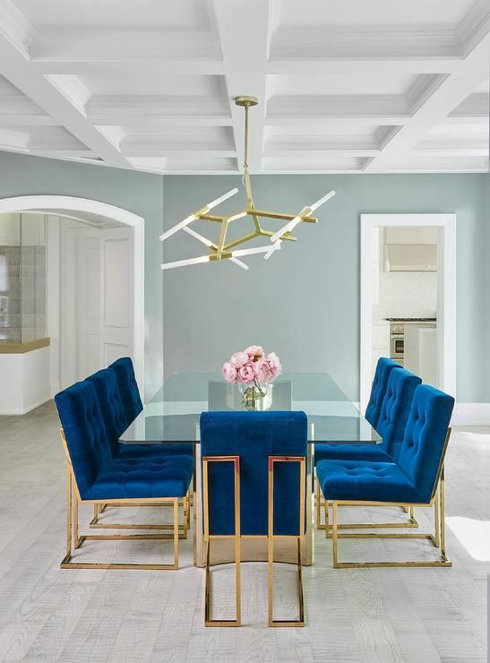 Jonathan Adler Goldfinger blue velvet dining chairs frame a stunning long glass  dining table with a