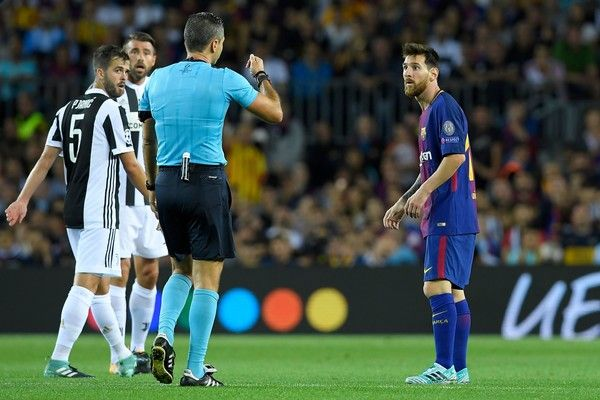 Barcelona's forward from Argentina Lionel Messi (R) receives a yellow card from referee during the UEFA Champions League Group D football match FC Barcelona vs Juventus at the Camp Nou stadium in Barcelona on September 12, 2017. / AFP PHOTO / LLUIS GENE