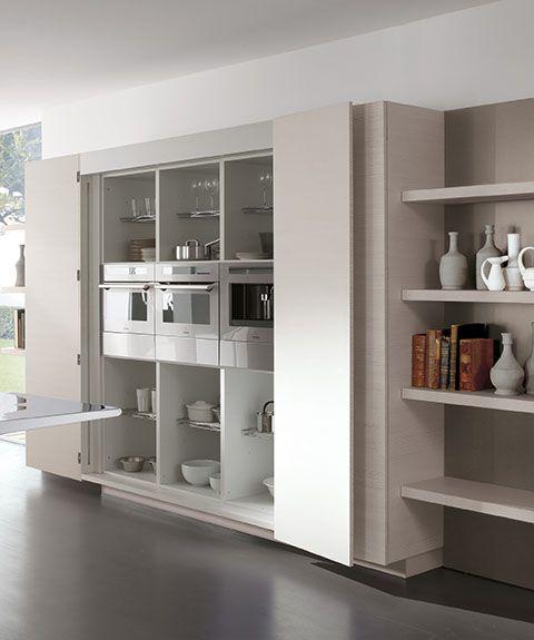 Muebles que ocultan hornos, capuchinera y nevera. Puertas en madera natural.