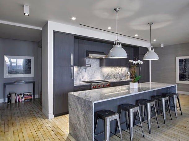 Cocina gris en un apartamento de Nueva York. El estudio Meshberg Group diseñó una estupenda cocina gris para la reforma de un apartamento de Nueva York, con puertas de roble teñidas de gris profundo. El proyecto estaba desarrollado siguiendo una composición en isla, con encimeras y pared frontal de cuarcita gris. Acompañan unas lámparas de pantalla metálica, pintada en gris, y unos taburetes a juego.  #Cocina