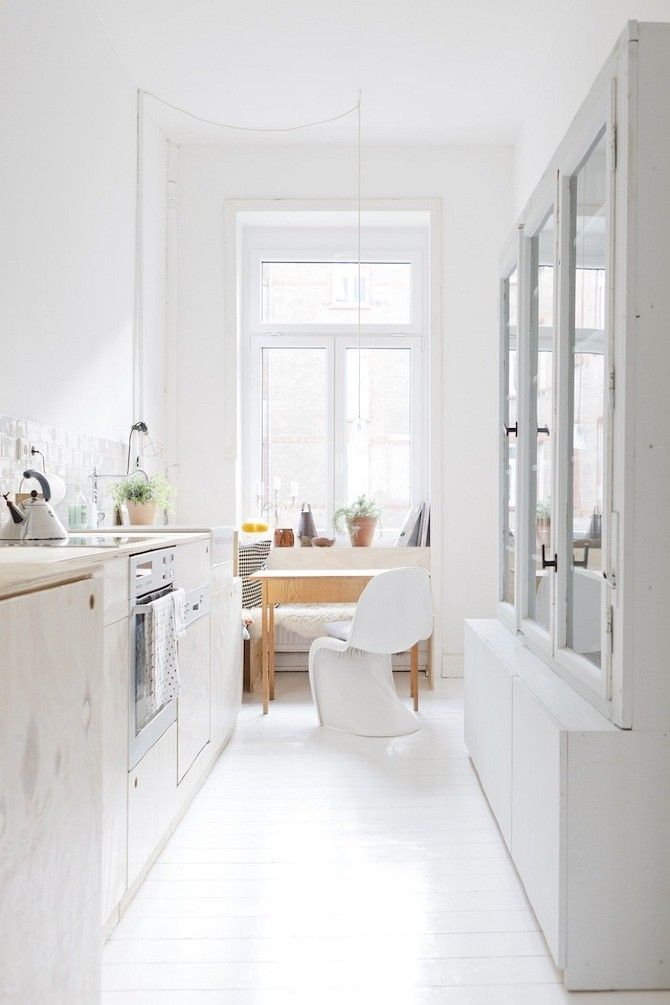 Kitchen with plywood cabinets, glass fronted cabinets, painted whtie floors and white Pantone chair in Wiesbaden Apartment by Studio Oink | Remodelista