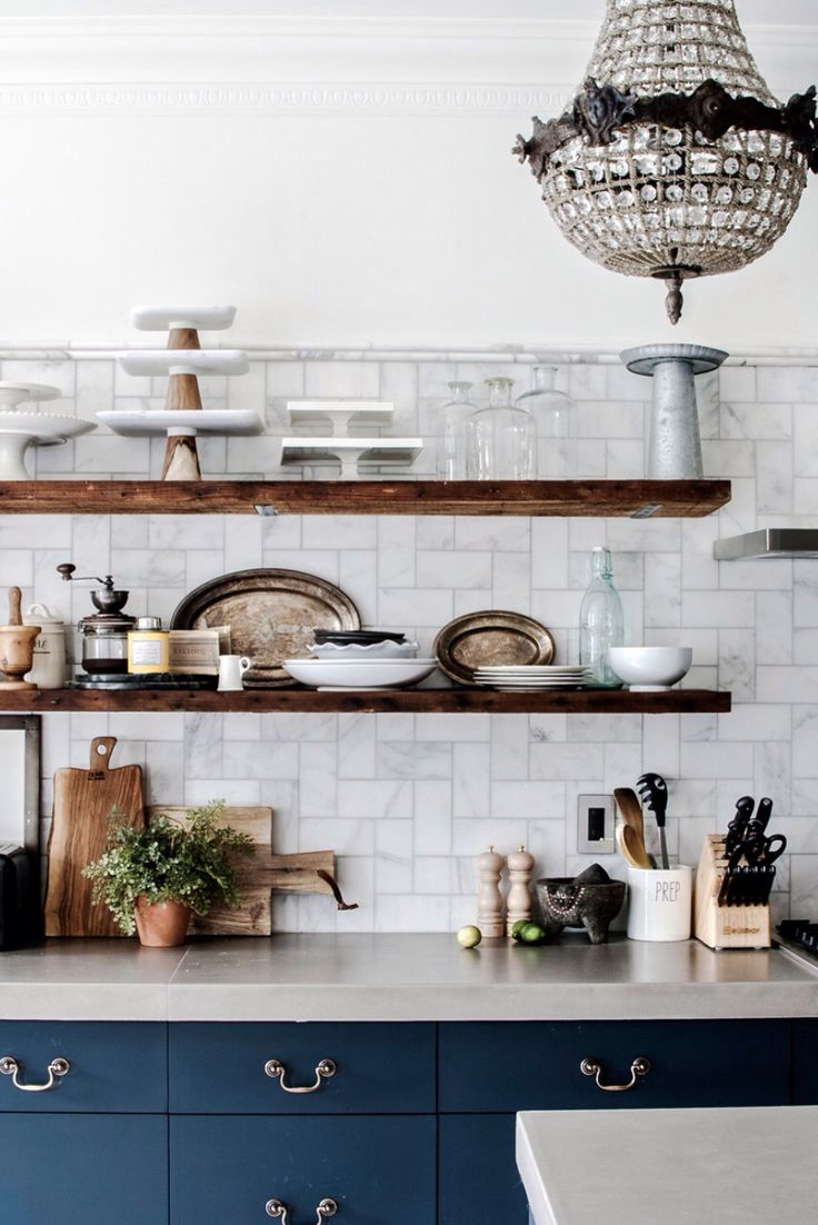 Midnight blue cabinets, Carrera marble subway tiles, reclaimed wood open shelving, vintage empire chandelier.