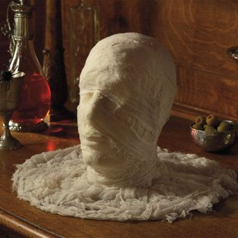 This head is dressed as a mummy and is surrounded by yards of gauze fabric, and makes a great Halloween party centerpiece on your buffet table.  Styrofoam head  Wrapped in cotton gauze