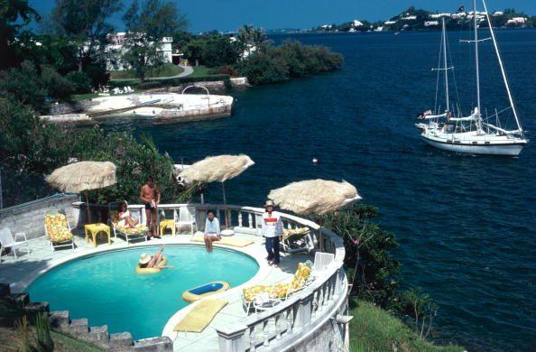 Bermuda Idyll (© Slim Aarons) Mrs Frank McMahon and guests around the pool at her seaside home in Bermuda, 1977.