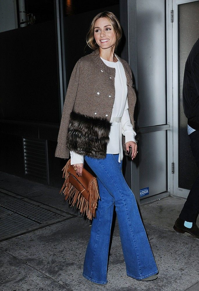 Olivia Palermo in a fur-hemmed sweater, flared jeans and a fringe clutch