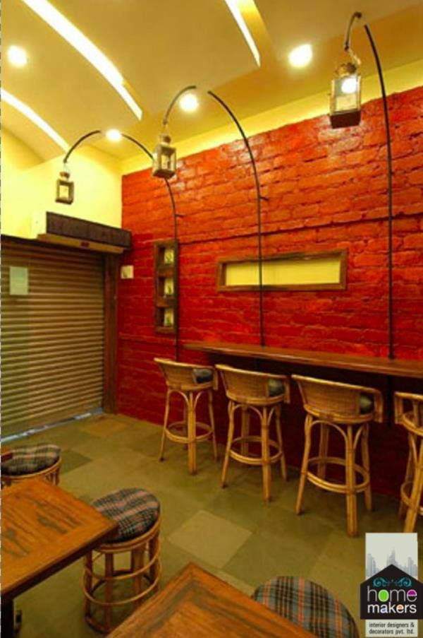 A very cool and trendy café designed exclusively by Home Makers Interior Designers & Decorators Pvt. Ltd.  We like to add some quirky elements in our designs which scream 'Home Makers', like the overhead lamp-post which act as really funky lighting.  The red brick wall adds a huge and interesting pop of colour.  Visit www.homemakersinterior.com for more!!