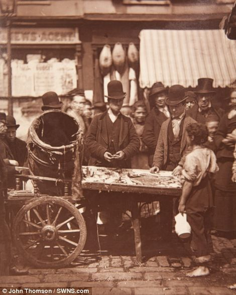 For sale: A fishmonger talks to customers at his stall, London.