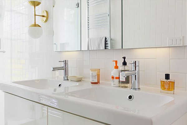 The D.S. & Durga couple opted for polished brass light fixtures to offset the muted tones and white on white textures in this Clinton Hill bathroom.
