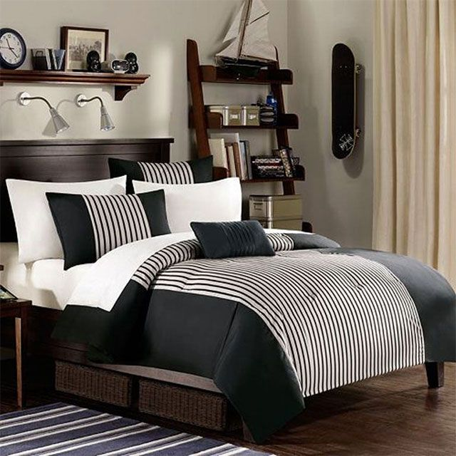Dormitorio estilo masculino, ropa de cama en tonos blanco y negro, cortinas color crema, repisa de madera y skate negro colgado en la pared
