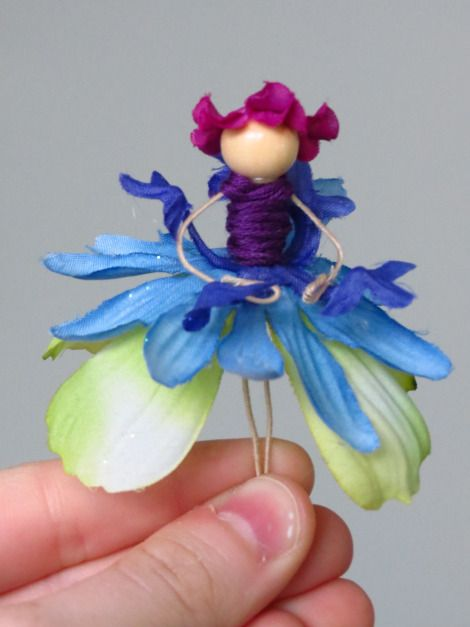 HOW TO MAKE FLOWER FAIRIES.   Fairy Wire (link above), glue gun, glue gun sticks, wooden medium sized beads in skin tone colors, other beads, faux flowers, glitter glue, and embroidery thread in different colors.