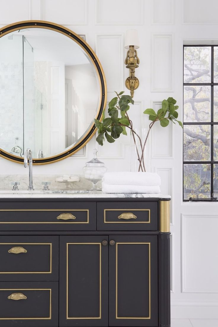 Bathroom detail from a Los Angeles residence by Kishani Perera, with a gorgeous round mirror, a classical washbasin.